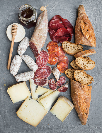 Cheese and meat appetizer selection or wine snack set. Variety of italian cheese, salami, bresaola, baguette and honey on over grey concrete backdrop, top view, vertical Banco de Imagens