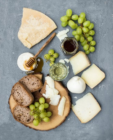 parmezan: Cheese appetizer selection or wine snack set. Variety of italian cheese, green grapes, bread slices and honey on round wooden board over grey concrete backdrop, top view, vertical