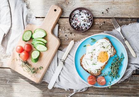 english cucumber: Breakfast set. Whole grain sandwich with fried egg, vegetables and herbs on rustic wooden table, morning mood, top view, horizontal Stock Photo
