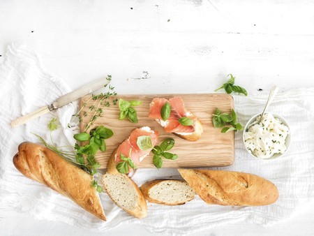 fish type: Salmon, ricotta and basil sandwiches with baguette on a rustic wooden board over white wood background. Top view, copy space