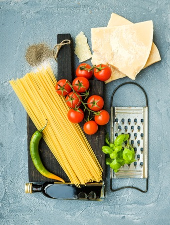 metal grater: Ingredients for cooking pasta. Spaghetti on dark wooden board, Parmesan cheese, cherry tomatoes, metal grater, olive oil and fresh basil on grey-blue concrete background, top view, vertical Stock Photo