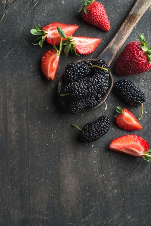 space wood: Berries on dark wooden background. Fresh strawberries and mulberries in rustic cooking spoon with copy space.
