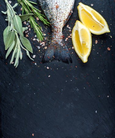 sea bream: Tail of fresh raw Dorado or sea bream fish on black slate stone board with spices, herbs, lemon and salt. Top view, copy space, vertical