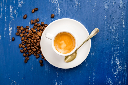 espresso: Cup of espresso coffee and beans on wooden blue painted table background. Top view Stock Photo