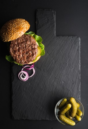 Fresh homemade burger on dark slate stone board, pickles and sliced onion over black background. Top view, copy space 스톡 콘텐츠
