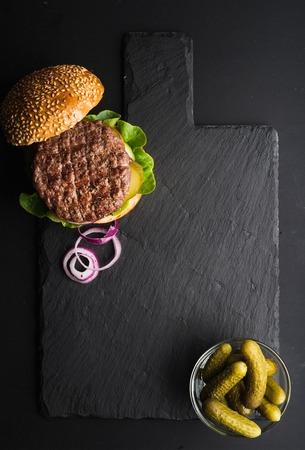 다크 슬레이트 돌 보드, 피 클 및 검정 배경 위에 얇게 썬된 양파에 신선한 수 제 햄버거. 상위 뷰, 복사본 공간