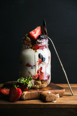 Yogurt oat granola with strawberries, mulberries, honey and mint leaves in tall glass jar on black backdrop, selective focus, vertical Reklamní fotografie