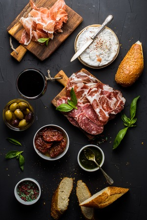 carne roja: Wine snack set. Glass of red, meat selection, mediterranean olives, sun-dried tomatoes, baguette slices, camembert cheese and spices on black background, top view