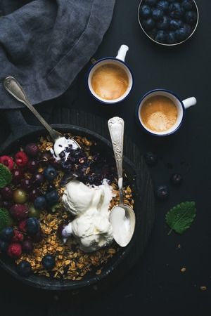 ice cram: Healthy breakfast. Oat granola crumble with fresh berries, seeds and ice-cream in iron skillet pan on dark wooden board and cups of coffee over black backdrop, top view, vertical