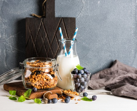 Healthy breakfast ingrediens. Homemade granola in open glass jar, milk or yogurt bottle, blueberries and mint on white table surface, concrete textured background, copy space