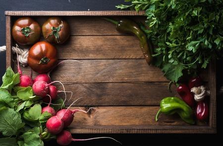 Verse rauwe plantaardige ingrediënten voor gezond koken of salade maken op rustieke houten achtergrond, bovenaanzicht, kopie ruimte. Dieet of vegetarisch voedselconcept. Stockfoto