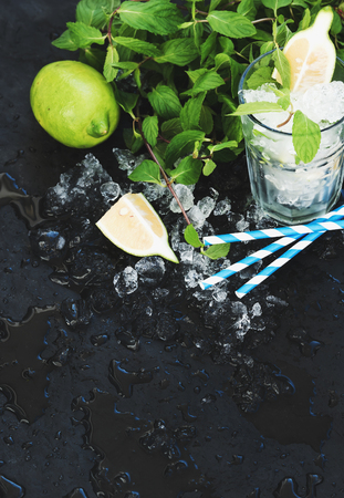 vetical: Mojito cooking set. Bunch of fresh mint, lime, chipped ice and coctail glass over black slate stone backdrop, selective focus, copy space