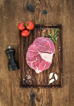 cross cut: Raw fresh beef meat cross cut for ossobuco cut with garlic cloves, cherry tomatoes, rosemary, pepper and salt on serving board over rustic wooden background, top view Stock Photo