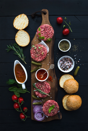 Ingredients for cooking burgers. Raw ground beef meat cutlets on wooden chopping board, buns, red onion, cherry tomatoes, greens, pickles, tomato sauce, cheese, herbs and spices over black background, top view
