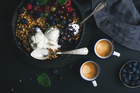 ice cram: Healthy breakfast. Oat granola crumble with fresh berries, seeds and ice-cream in iron skillet pan on dark wooden board and cups of coffee over black backdrop, top view