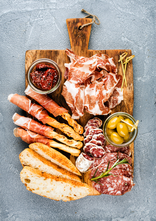delicatessen: Meat appetizer selection or wine snack set. Variety of smoked meat, salami, prosciutto, bread sticks, baguette, olives and sun-dried tomatoes on rustic wooden board over grey concrete textured backdrop, top view.