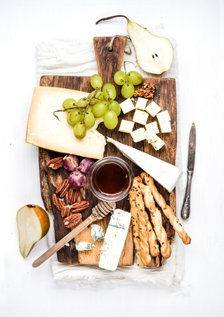 Cheese appetizer set. Various types of cheese, honey, grapes, pear, nuts and bread grissini sticks on rustic wooden board over white background, top view Фото со стока