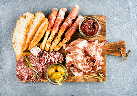 Meat appetizer selection or wine snack set. Variety of smoked meat, salami, prosciutto, bread sticks, baguette, olives and sun-dried tomatoes on rustic wooden board, top view, horizontal Stock Photo