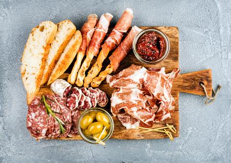 Vlees voorgerecht selectie of wijn snack set. Verscheidenheid van gerookte vlees, salami, prosciutto, brood stokken, stokbrood, olijven en zongedroogde tomaten op rustieke houten bord, bovenaanzicht, horizontale