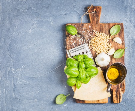 metal grater: Ingredients for cooking Pesto sauce. Parmesan cheese, metal grater, fresh basil, olive oil, garlic and pine nuts on old rustic wooden board over grey concrete background, top view, copy space