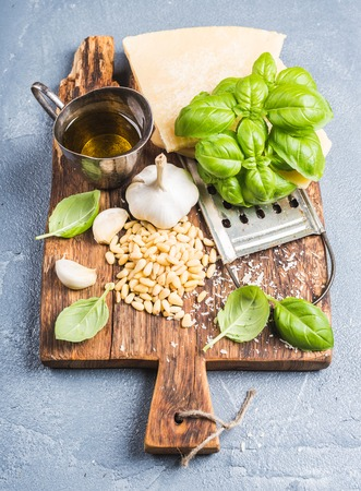 metal grater: Ingredients for cooking Pesto sauce. Parmesan cheese, metal grater, fresh basil, olive oil, garlic and pine nuts on old rustic wooden board over grey concrete background,selective focus, vertical Stock Photo
