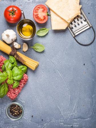 verticales: Ingredientes para cocinar la pasta boloñesa. Espagueti, queso parmesano, tomates, rallador de metal, aceite, ajo, carne picada, la pimienta y la albahaca en el fondo de hormigón gris, vista desde arriba, copia espacio, vertical Foto de archivo