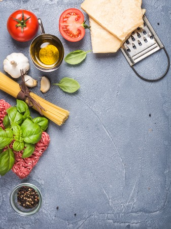 recipe background: Ingredients for cooking pasta Bolognese. Spaghetti, Parmesan cheese,  tomatoes, metal grater, oil, garlic, minced meat, pepper and basil on grey concrete background, top view, copy space, vertical
