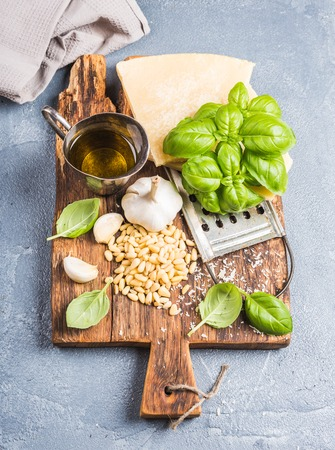 metal grater: Ingredients for cooking Pesto sauce. Parmesan cheese, metal grater, fresh basil, olive oil, garlic and pine nuts on old rustic wooden board over grey concrete background, top view, vertical