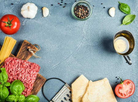 metal grater: Ingredients for cooking pasta Bolognese. Spaghetti, Parmesan cheese,  tomatoes, metal grater, oil, garlic, minced meat, pepper and basil on grey concrete background, top view, copy space Stock Photo
