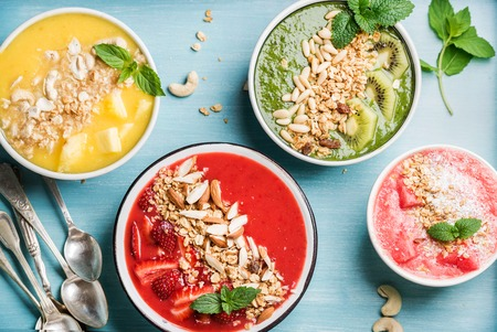 breakfast bowl: Healthy summer breakfast concept. Colorful fruit smoothie bowls with nuts and oat granola on turquoise blue background . Yellow, red, green, pink. Top view, horizontal