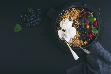 ice cram: Healthy breakfast. Oat granola crumble with fresh berries, seeds and ice-cream in iron skillet pan on dark wooden board over black backdrop, top view, horizontal Stock Photo
