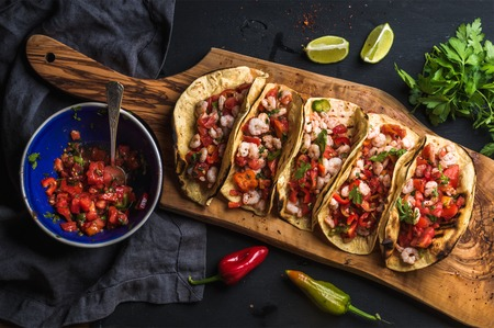 Shrimp tacos with homemade salsa, limes and parsley on wooden board over dark background. Top view. Mexican cuisine Banco de Imagens