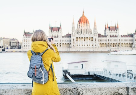blondy: Young blondy woman tourist making photos of Parliament historic building from Danube side with her phone in Budapest, Hungary, on a spring clear day