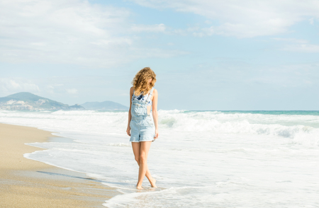 Young woman in blue denim jumpsuit walking along beach and the stormy sea sunny day