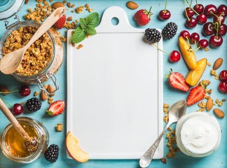 Healthy breakfast ingredients. Oat granola in open glass jar, yogurt, fruit, berries, honey and mint on blue background with white ceramic board in center, top view, copy space