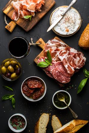 Wijn snack te stellen. Glas rode, vlees selectie, mediterrane olijven, zongedroogde tomaten, stokbrood plakjes, camembert kaas en kruiden op zwarte achtergrond, bovenaanzicht