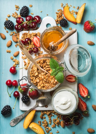 Healthy breakfast ingredients. Oat granola in open glass jar, yogurt, fruit, berries, honey and mint on blue background with white ceramic board in center, top view