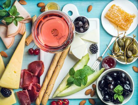 pan y vino: establece aperitivo vino de verano. Copa de vino rosado, carne, queso, aceitunas, miel, palitos de pan, frutos secos, alcaparras y las bayas con la placa de cerámica blanca en el centro, fondo de madera azul, vista desde arriba Foto de archivo