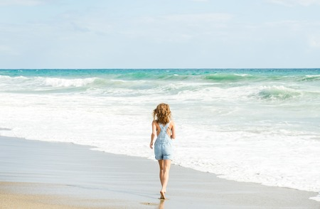 jumpsuite: Young woman in blue denim jumpsuit walking towards stormy sea
