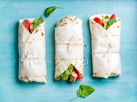 건강한 점심 식사. 옥수수 구운 치킨 필렛과 파란색 페인트 나무 배경에 신선한 야채와 함께 랩합니다. 평면도