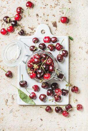 cherries isolated: Sweet cherry in glass jar on white ceramic board over concrete background, top view