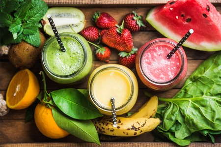 Freshly blended fruit smoothies of various colors and tastes in glass jars in rustic wooden tray. Yellow, red, green. Top view, selective focus Standard-Bild