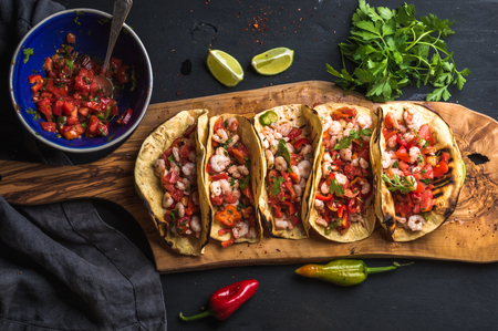 Shrimp tacos with homemade salsa, limes and parsley on wooden board over dark background. Top view. Mexican cuisine 스톡 콘텐츠
