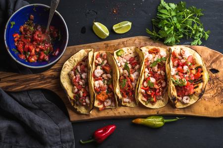 tacos de camarón con salsa casera, limas y el perejil en la tabla de madera sobre fondo oscuro. Vista superior. cocina mexicana
