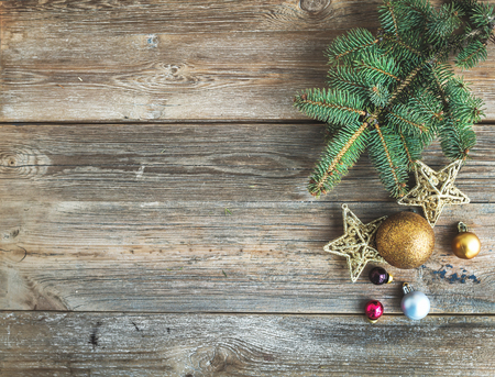 copy space: Christmas or New Year rustic wooden background with toy decorations and fur tree branch, top view, copy space