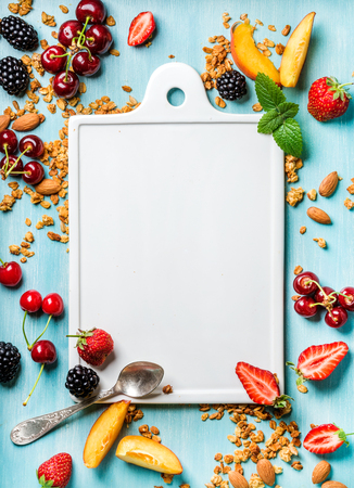 Healthy breakfast ingredients. Oat granola, fruit, berries and mint on blue background with white ceramic board in center, top view, copy space Standard-Bild