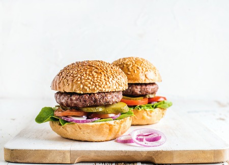bbq background: Fresh homemade burgers on wooden serving board with onion rings. White background, selective focus, copy space