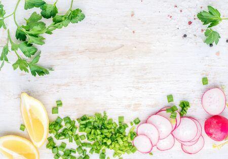 健康的な食材と木製キッチン テーブル背景をホワイト スペースをコピーしてください。野菜とハーブのサラダ。大根、ネギ、パセリ、レモン。トップ ビュー 写真素材