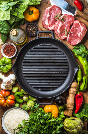 Ingredients for cooking healthy meat dinner. Raw uncooked beef steaks with vegetables, rice, herbs, spices and wine bottle over rustic wooden background, cast irom grilling pan in center. Top view, copy space