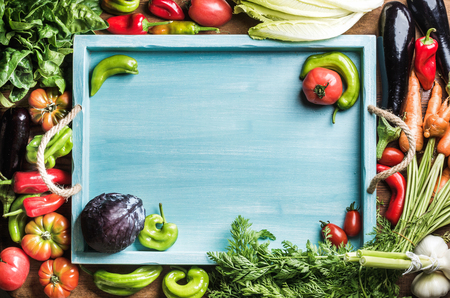 vegetable tray: Fresh raw vegetable ingredients for healthy cooking or salad making with blue wooden tray in center, top view, copy space. Diet or vegetarian food concept, horizontal composition Stock Photo